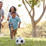 Family playing soccer in park.