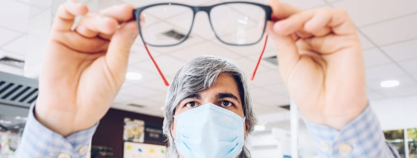Man wearing mask trying on glasses.